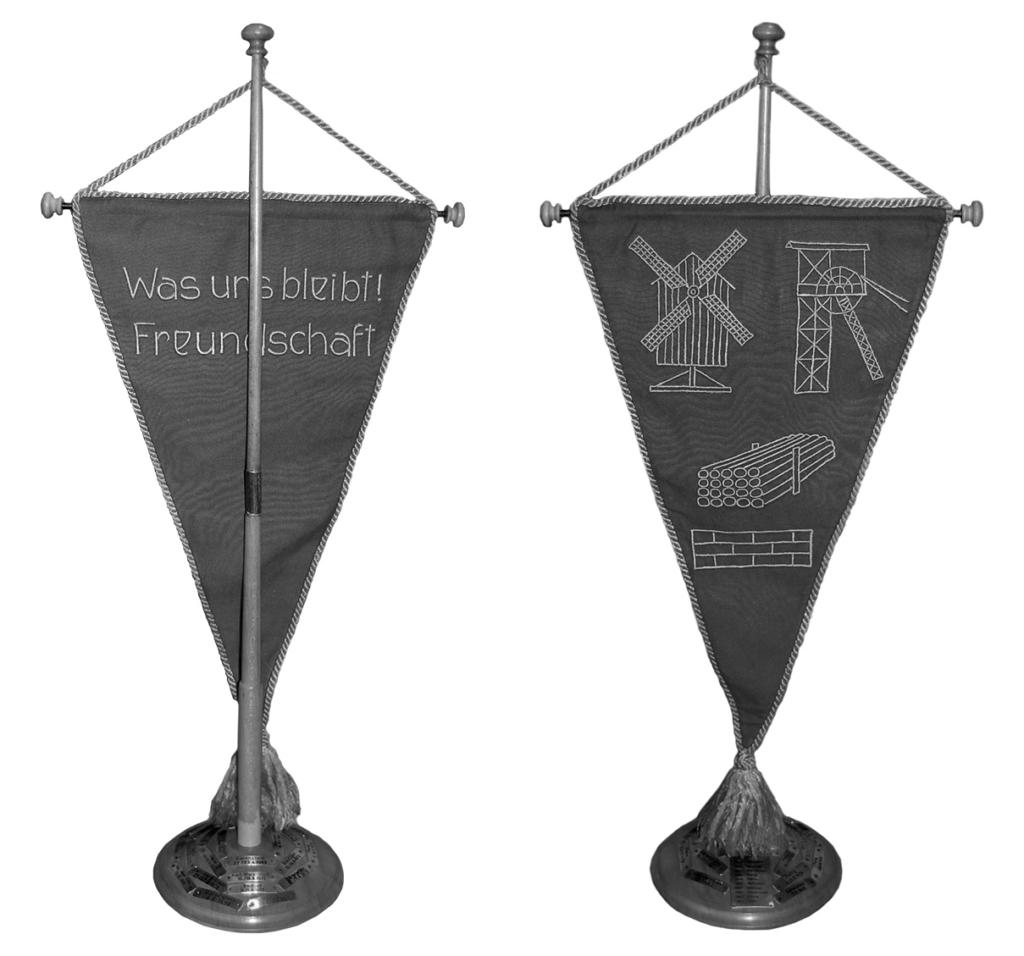 Foto der Wimpel der fünf Freunde. Eine Mühle steht für das sowjetische Speziallagespanspanspanspanspanspanspanspanspanspanspanspanspanspanspanspanspanspanspanspanspanspanspanspanspanspanspanspanspanspanspanspanspanspanr Nr. 1/span/span/span/span/span/span/span/span/span/span/span/span/span/span/span/span/span/span/span/span/span/span/span/span/span/span/span/span/span/span/span/span/span/span Mühlberg, der Förderturm für den Steinkohlebergbau in Sibirien, ein Stapel Holz für das Sägewerk in Stalinsk und eine Ziegelsteinmauer für die Zeit, in der sie hauptsächlich als Maurer tätig waren.